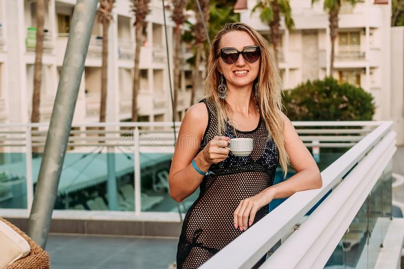 Uśmiechnięta kobieta na wakacje z filiżanka kawy zdjęcia stock