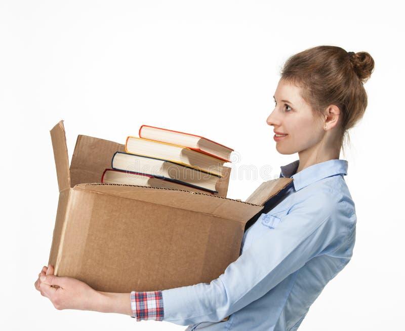 Uśmiechnięta kobieta niesie karton z książkami zdjęcie royalty free