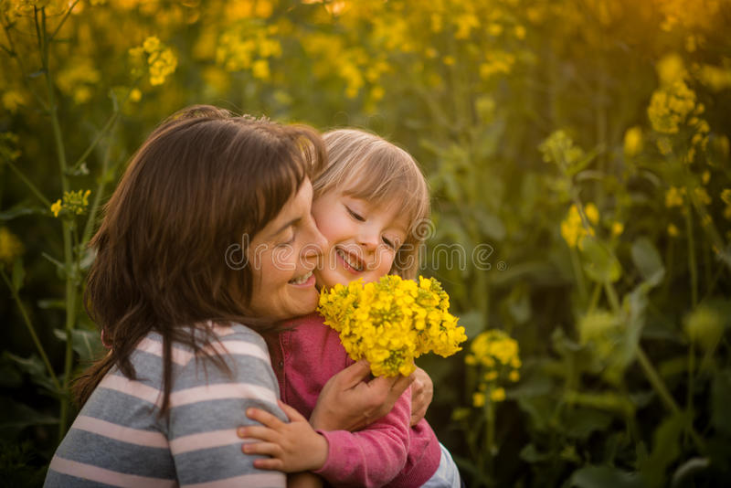 Uśmiechnięta kobieta obejmuje jej ślicznej córki, outdoors fotografia stock