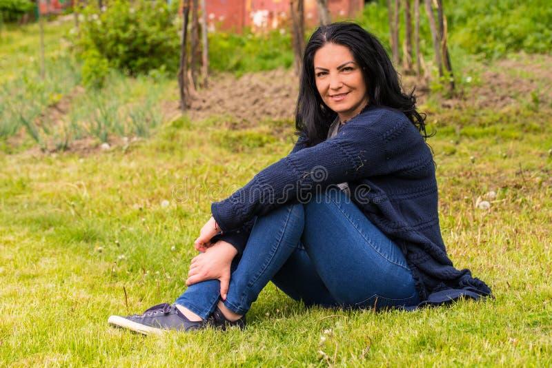 Uśmiechnięta kobieta odpoczywa w ogródzie fotografia royalty free