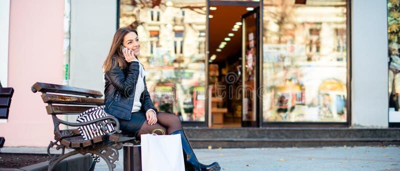 Uśmiechnięta kobieta opowiada na telefonie komórkowym po robić zakupy obraz stock