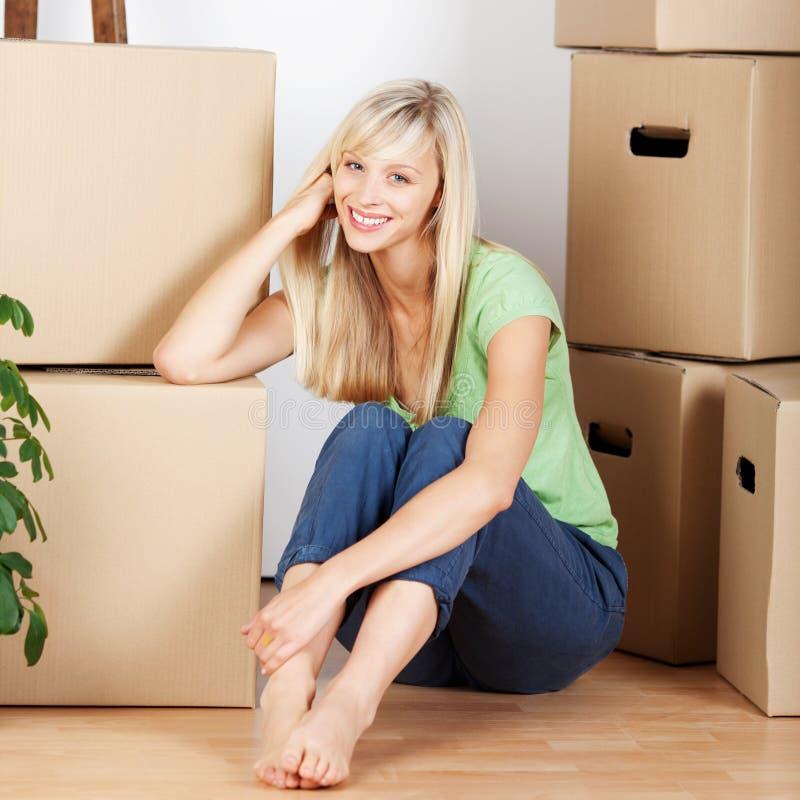 Uśmiechnięta kobieta otaczająca kartonowymi kartonami obrazy stock