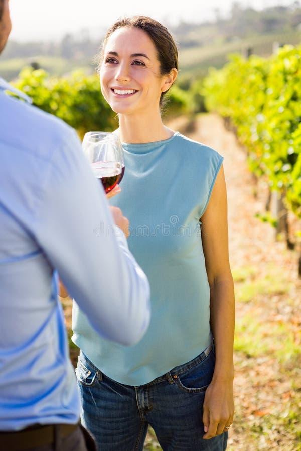 Uśmiechnięta kobieta patrzeje mężczyzna mienia wineglass fotografia stock