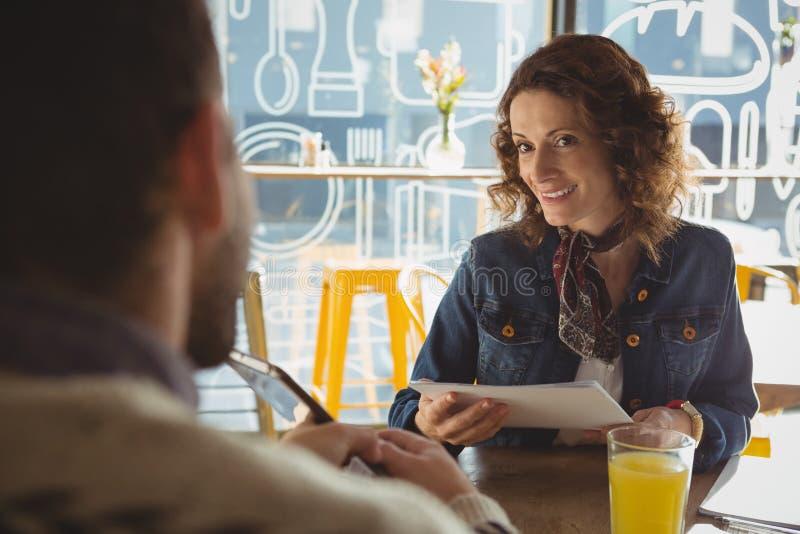 Uśmiechnięta kobieta patrzeje mężczyzna w kawiarni z dokumentem zdjęcia stock