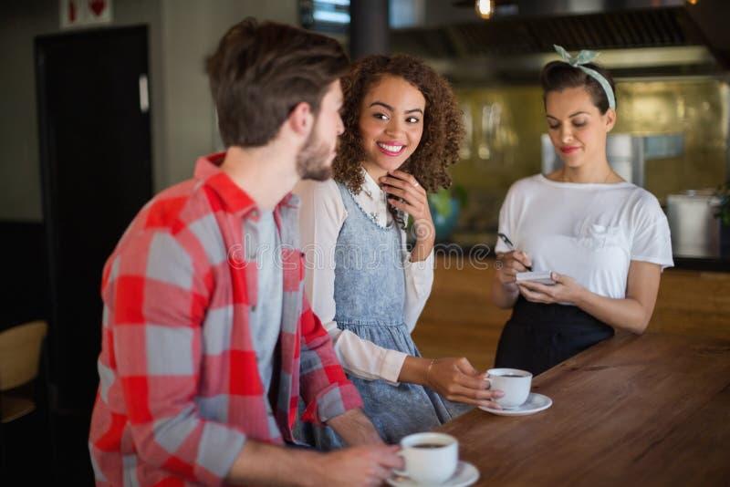 Uśmiechnięta kobieta patrzeje przyjaciela podczas gdy umieszczający rozkaz kelnerka fotografia royalty free