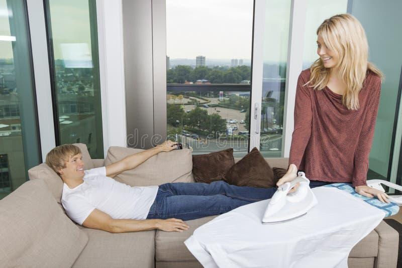 Uśmiechnięta kobieta patrzeje zrelaksowany podczas gdy odprasowywający koszula w żywym pokoju w domu obrazy royalty free