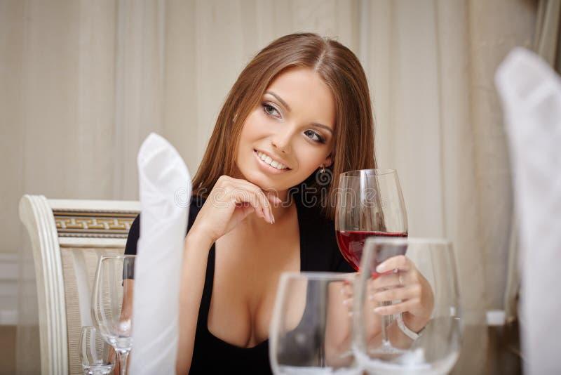 Uśmiechnięta kobieta pije aperitif w restauraci zdjęcie stock