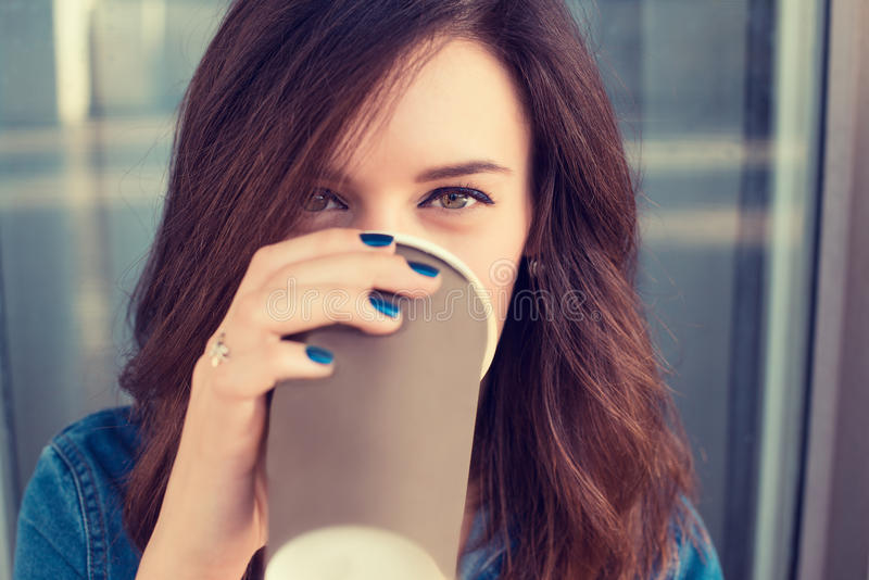 Uśmiechnięta kobieta pije kawowego mienia papierową filiżankę fotografia royalty free