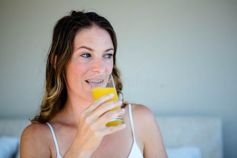 uśmiechnięta kobieta pije szkło sok pomarańczowy obraz royalty free