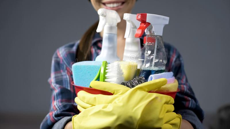 Uśmiechnięta kobieta podnosi w górę wiadra z mnogimi gospodarstwa domowego cleaning substancjami zdjęcia stock
