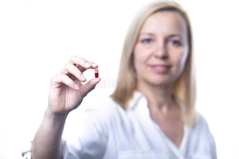 Uśmiechnięta kobieta pokazuje kapsuły pastylkę Ostrość na kapsule fotografia stock