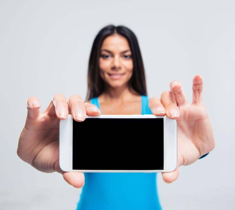 Uśmiechnięta kobieta pokazuje pustego smartphone ekran obrazy stock