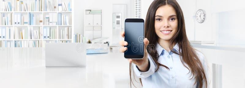 Uśmiechnięta kobieta pokazuje smartphone odizolowywającego na wewnętrznym biurowym busin zdjęcia royalty free