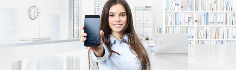Uśmiechnięta kobieta pokazuje smartphone odizolowywającego na wewnętrznym biurowym busin obraz stock