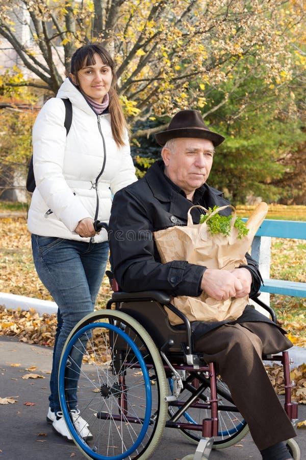 Uśmiechnięta kobieta pomaga jej niepełnosprawnego ojca obraz royalty free