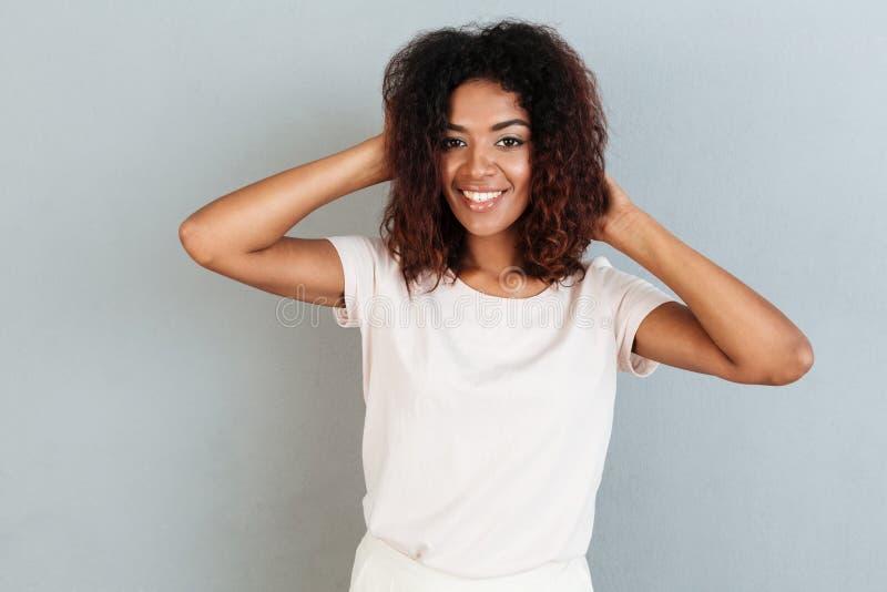 Uśmiechnięta kobieta pozuje i bawić się z jej włosy podczas gdy stojący obraz royalty free