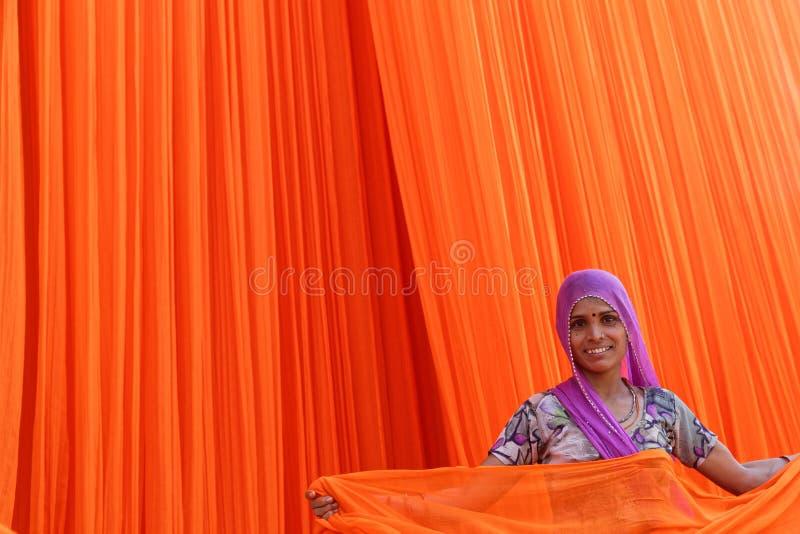 Uśmiechnięta kobieta pracuje w tekstylnej fabryce zdjęcie stock
