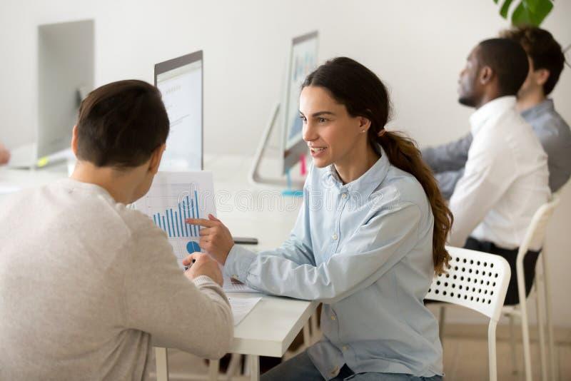 Uśmiechnięta kobieta przedstawia pieniężnego wykres męski biznesowy colle zdjęcie royalty free