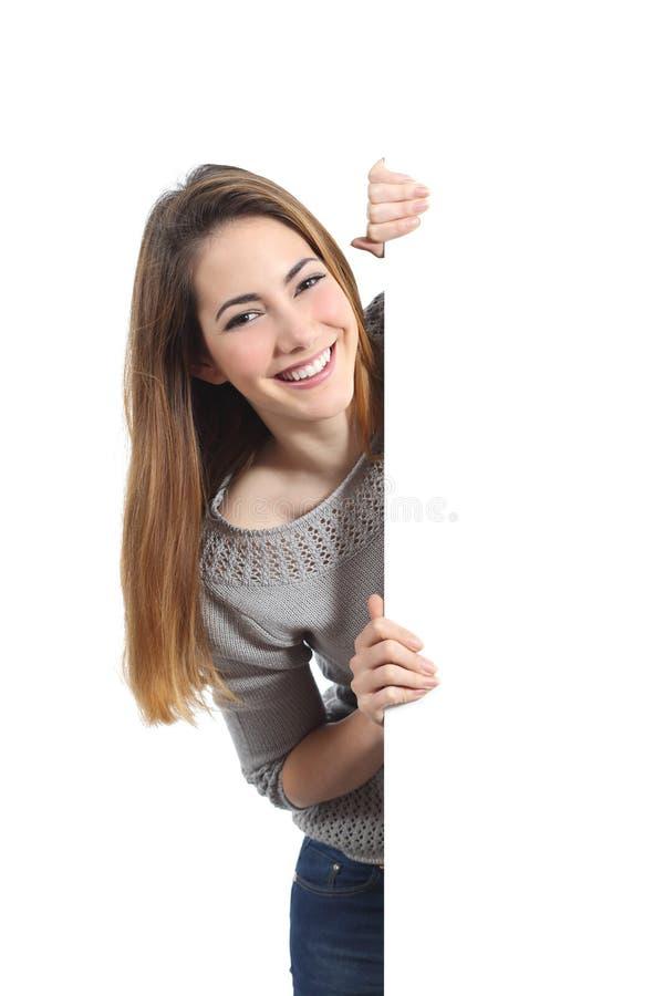 Uśmiechnięta kobieta przedstawia pustego znaka i trzyma zdjęcia stock
