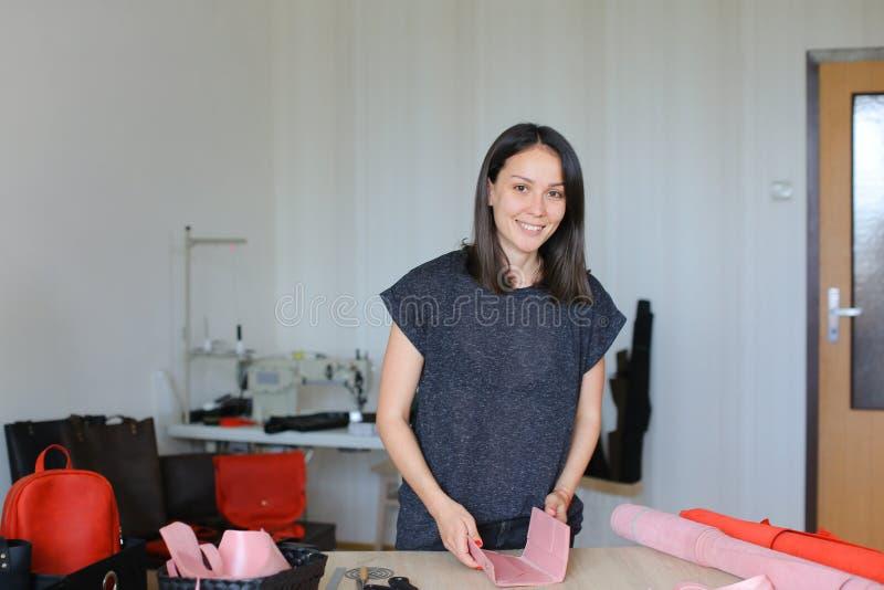 Uśmiechnięta kobieta robi różowemu rzemiennemu portfla atelier w domu zdjęcie royalty free