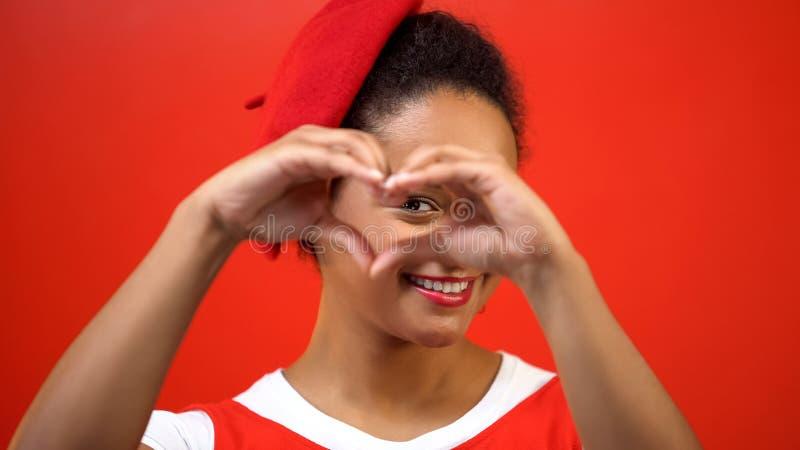 Uśmiechnięta kobieta robi sercu podpisywać rękami na czerwonym tle, dobroć, dobroczynność fotografia stock