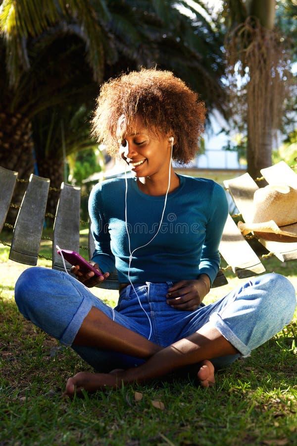 Uśmiechnięta kobieta słucha muzyka z telefonem komórkowym obrazy royalty free