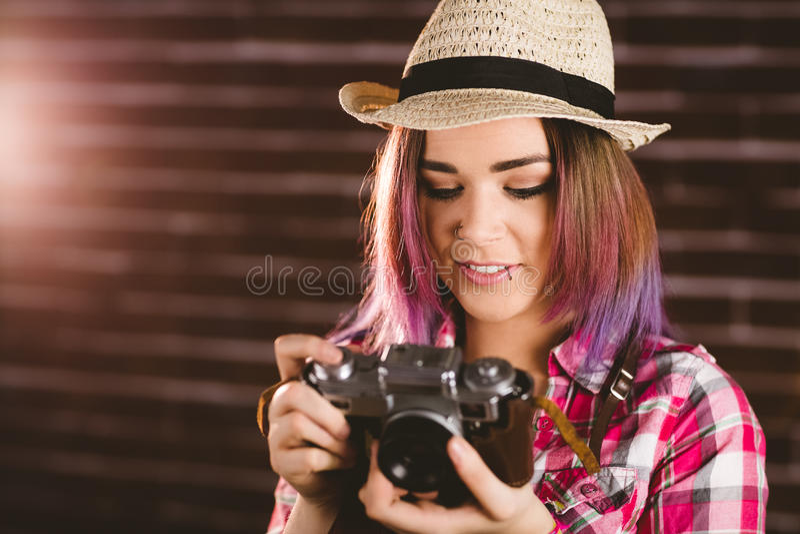 Uśmiechnięta kobieta sprawdza fotografie od rocznik kamery zdjęcia stock