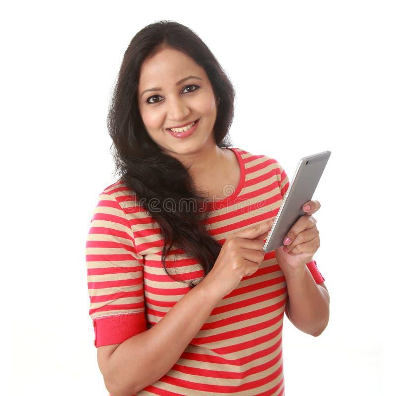 Uśmiechnięta kobieta texting z jej telefonem komórkowym przeciw bielowi obrazy royalty free