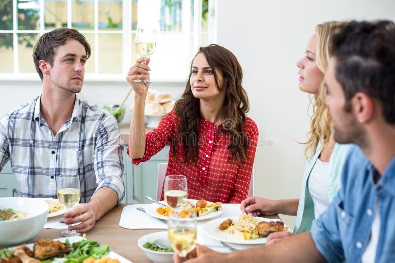 Uśmiechnięta kobieta trzyma białego wina szkło z przyjaciółmi fotografia stock