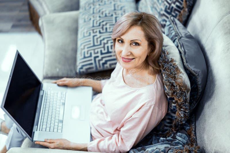 Uśmiechnięta kobieta trzyma laptop pracuje od domu zdjęcia stock