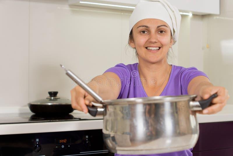 Uśmiechnięta kobieta trzyma out gotować garnek obrazy royalty free