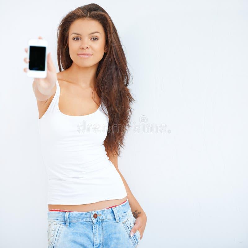 Uśmiechnięta kobieta trzyma out jej telefon komórkowego obraz royalty free