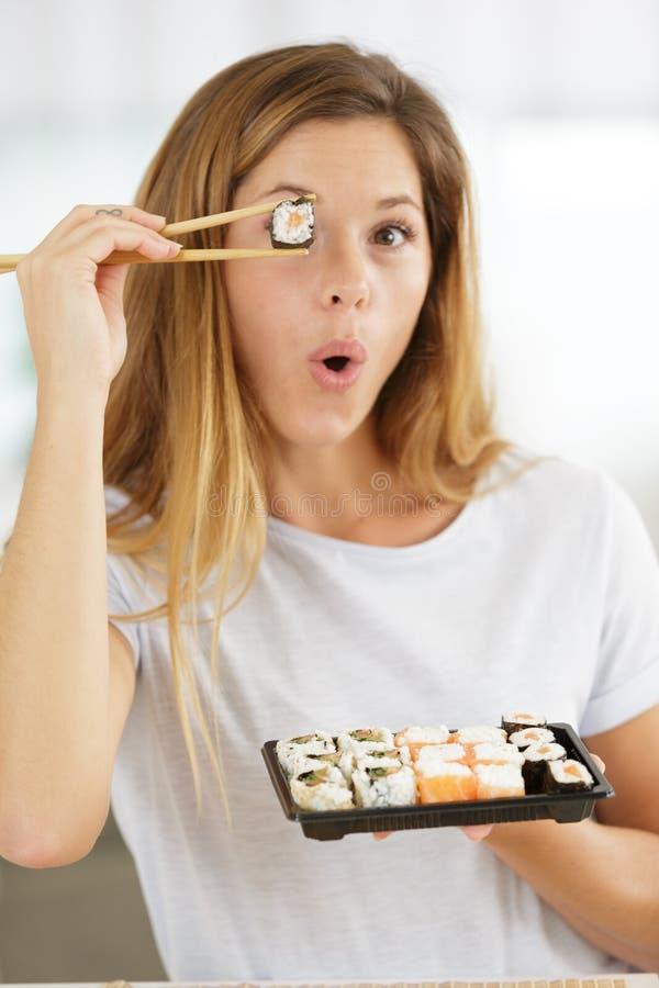 Uśmiechnięta kobieta trzymająca sushi w oczach z pałeczkami zdjęcie royalty free