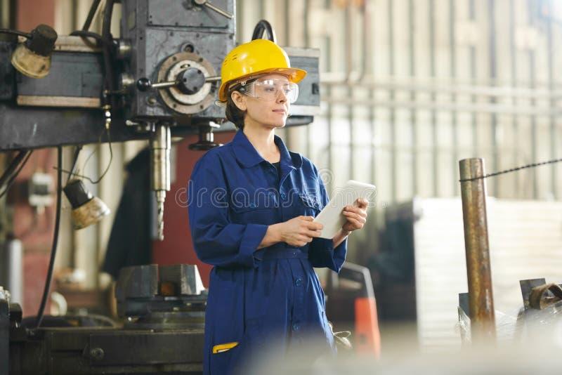 Uśmiechnięta kobieta Używa pastylkę przy fabryką zdjęcie stock