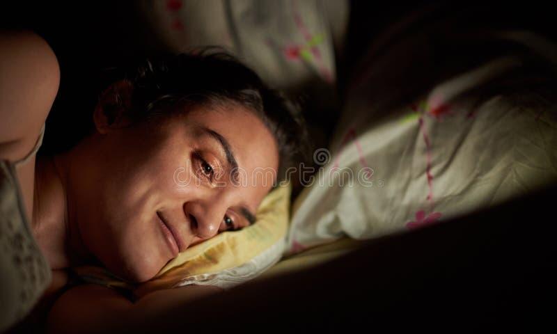 Uśmiechnięta kobieta używa pastylkę w łóżku obrazy royalty free