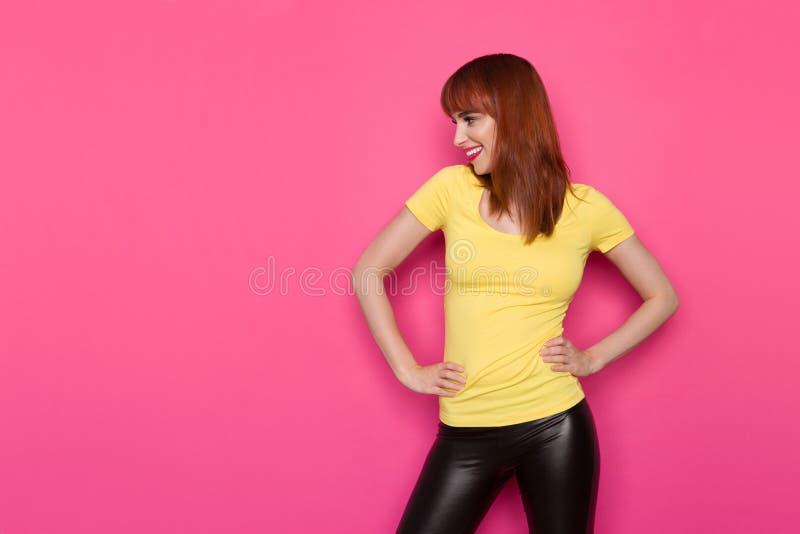 Uśmiechnięta kobieta W Żółtej koszula Trzyma ręki Na Modnym I Patrzeje Daleko od obrazy royalty free