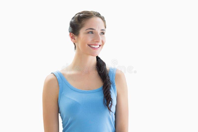 Uśmiechnięta kobieta w błękitnym podkoszulku bez rękawów patrzeje daleko od zdjęcia stock