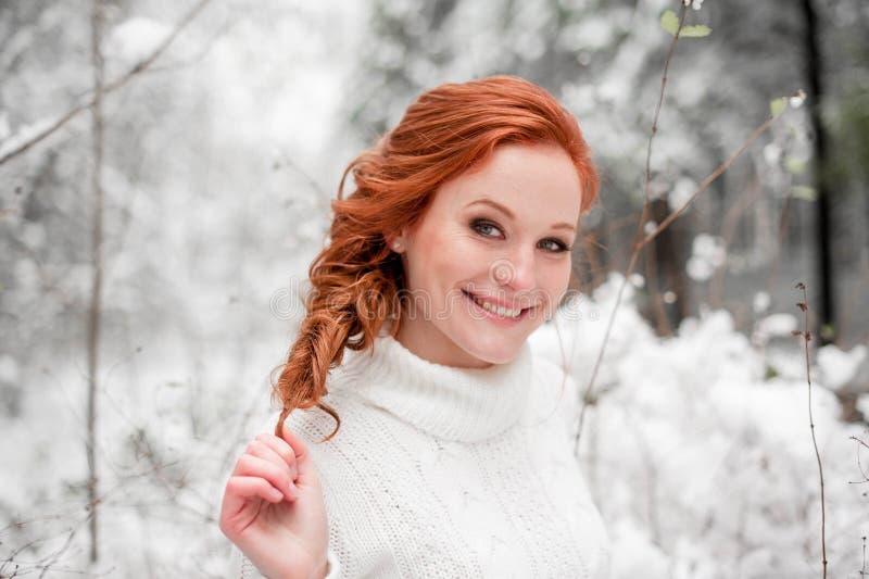 Uśmiechnięta kobieta w białym pulowerze w śnieżnym lesie zdjęcia stock