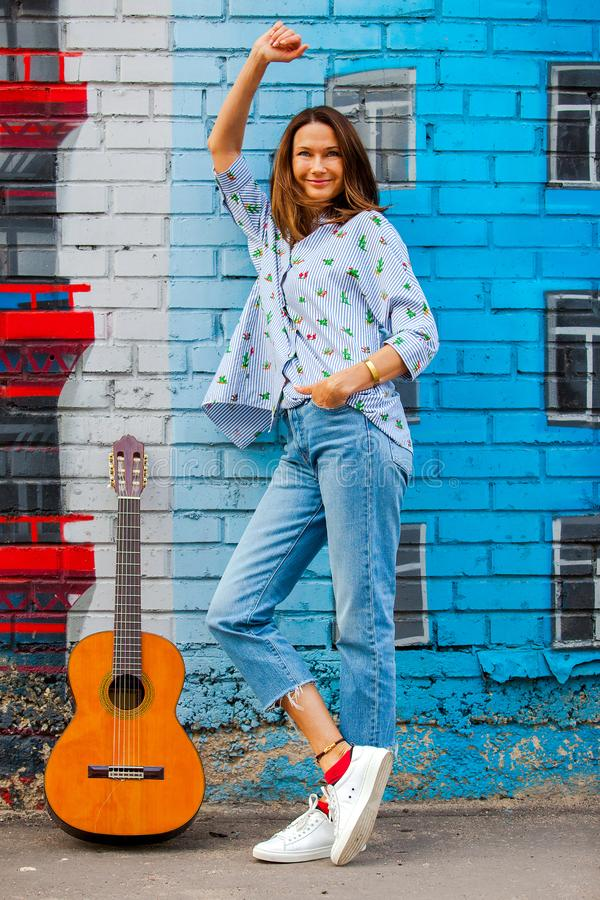 Uśmiechnięta kobieta w cajgach stoi blisko ściany z graffiti obok Gu obraz stock