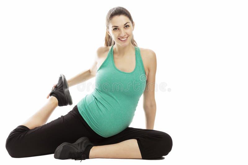 Uśmiechnięta kobieta w ciąży, brunetka, wykonuje fizycznych ćwiczenia na podłodze pojedynczy bia?e t?o miejsce tekst zdjęcia stock