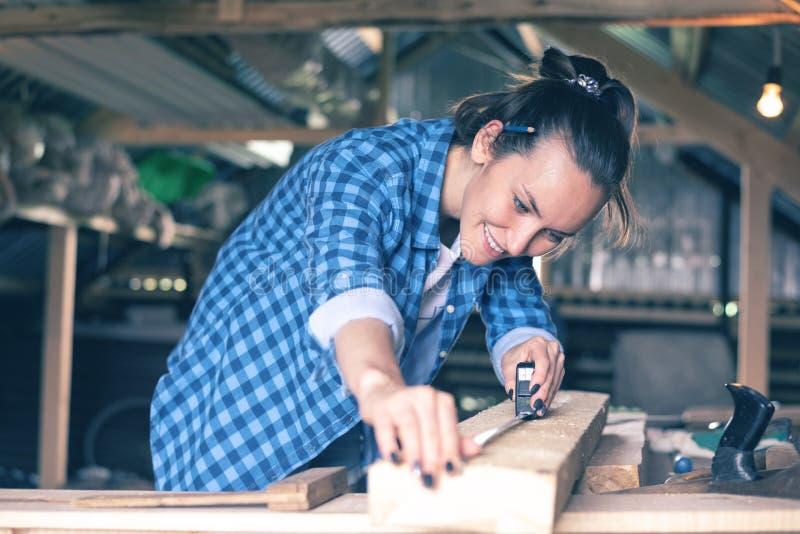 Uśmiechnięta kobieta w domowej warsztatowej pomiarowej taśmy miarze drewniana deska przed piłować, ciesielka obrazy royalty free