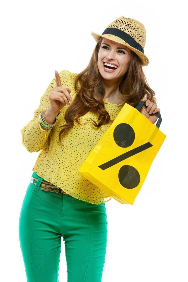 Uśmiechnięta kobieta w kapeluszowym pokazuje torba na zakupy i wskazywać na boku fotografia stock