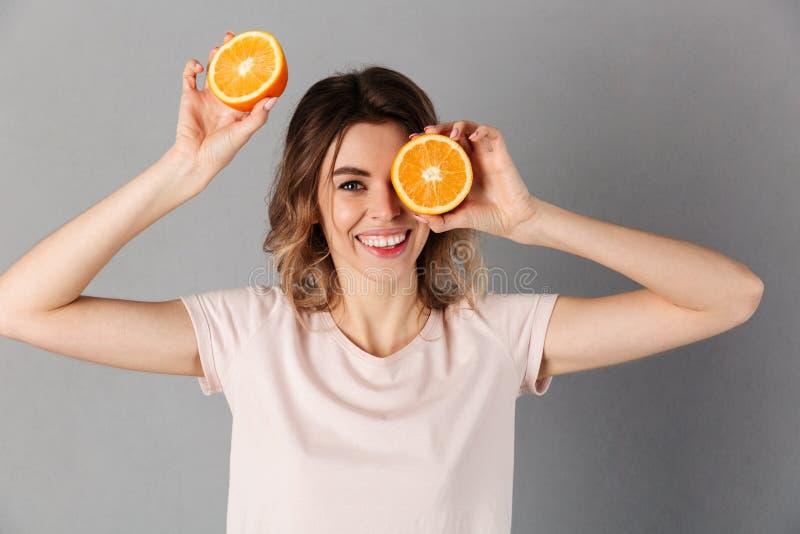 Uśmiechnięta kobieta w koszulce bawić się z pomarańczami obrazy royalty free