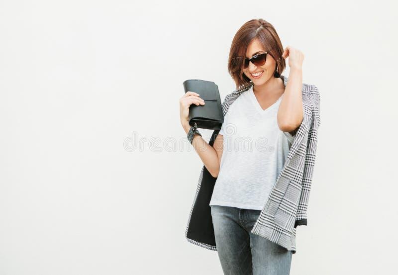Uśmiechnięta kobieta w monochromatycznym przypadkowym stroju z w kratkę kurtką obrazy stock
