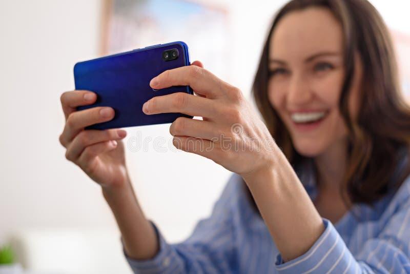 Uśmiechnięta kobieta w niebieskiej koszuli rozmawia przez telefon, wideorozmowy, bierze selfie, gra online obraz stock