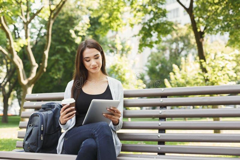 Uśmiechnięta kobieta w parku używać cyfrową pastylkę zdjęcie royalty free