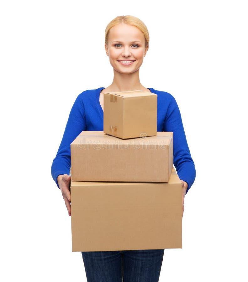 Uśmiechnięta kobieta w przypadkowych ubraniach z drobnicowymi pudełkami fotografia stock
