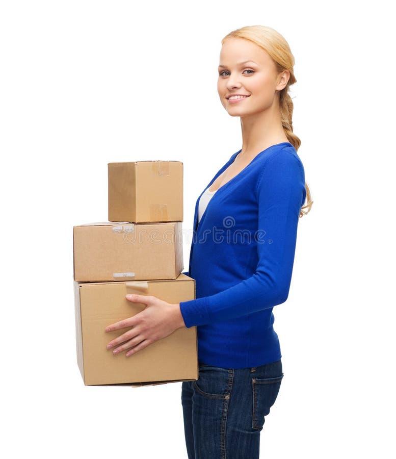 Uśmiechnięta kobieta w przypadkowych ubraniach z drobnicowymi pudełkami obrazy stock