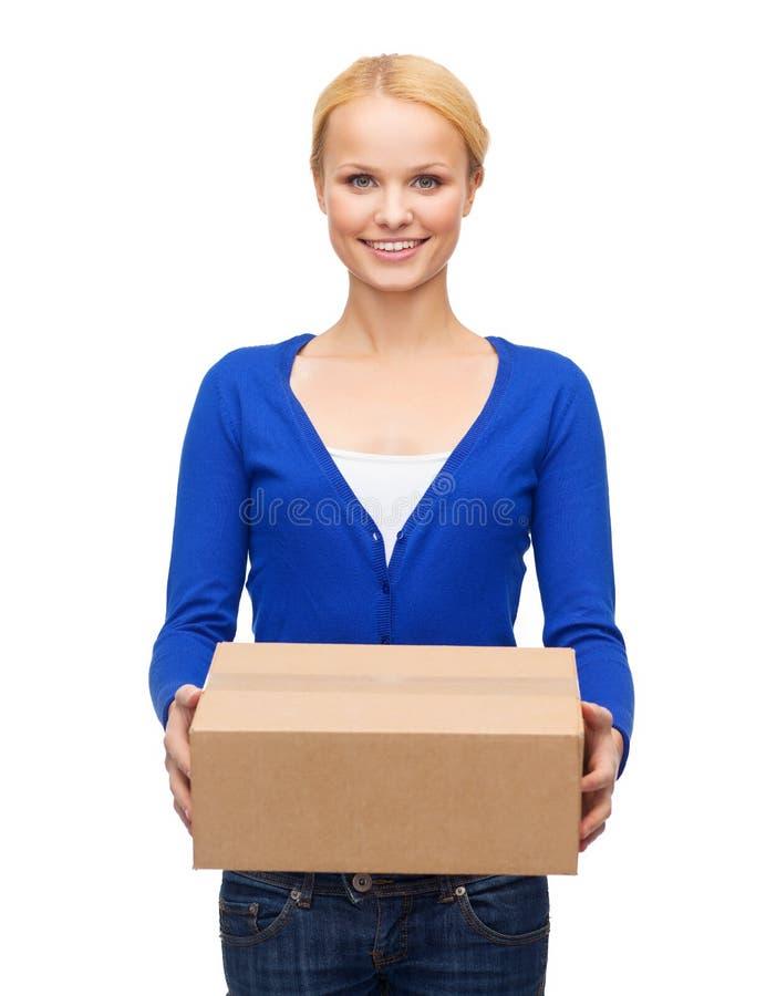 Uśmiechnięta kobieta w przypadkowych ubraniach z pakuneczka pudełkiem zdjęcie stock