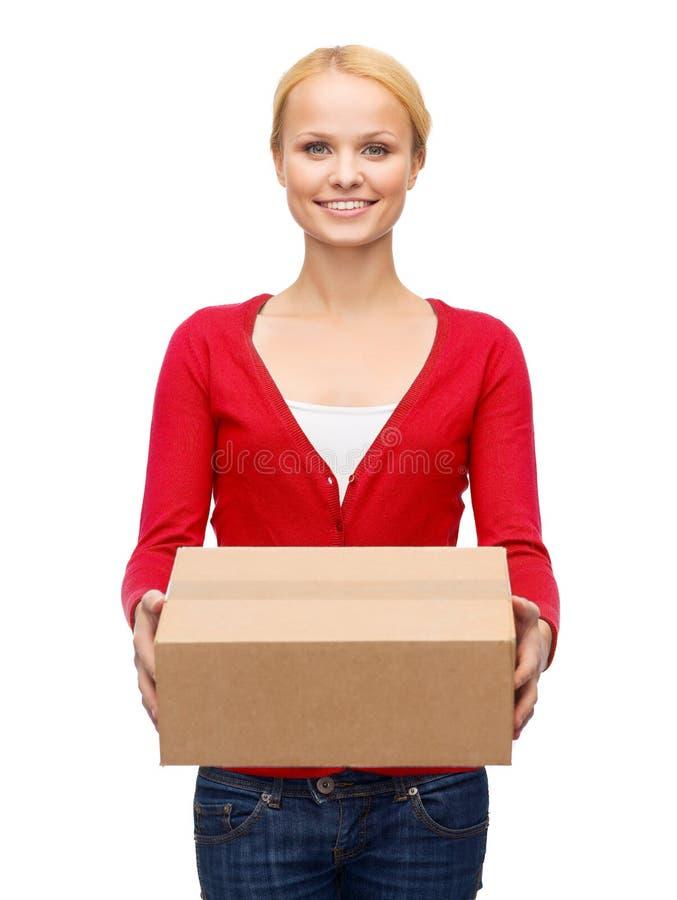 Uśmiechnięta kobieta w przypadkowych ubraniach z pakuneczka pudełkiem obraz stock